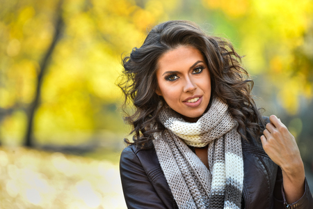 Portrait of beautiful young woman outdoors in a autumn day.