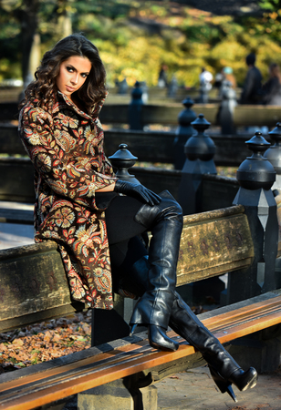 Fashion autumn outdoor photo of sexy beautiful woman with dark curly hair wearing coat and high heels boots posing in the park.