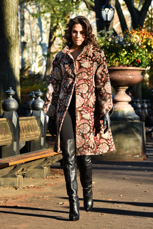 Elegant young woman walking  in autumn park wearing fashionable coat, gloves and  high heel boots.