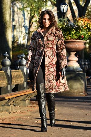 Elegante jonge vrouw lopen in het najaar park dragen van modieuze jas, handschoenen en hoge hak laarzen. Stockfoto