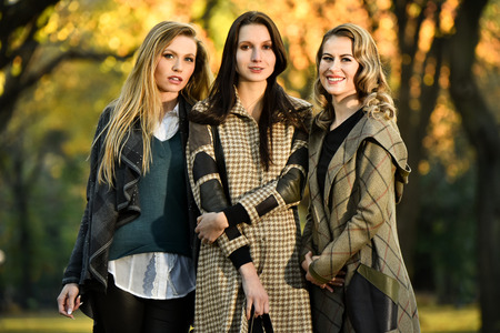 fashion: Three beautiful young fashion models posing against the backdrop of the autumn park.