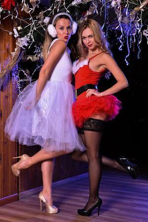 helpers: Two young girls posing in front of camera as Sexy Santa Helpers wearing holiday dresses, lingerie and hi-heels