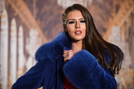Beautiful young woman with long brown hair and bright evening makeup. Closeup portrait of a fashion model in luxury fur coat.