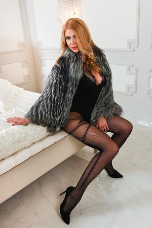 Elegant  blonde woman in seductive black lingerie bodysuit and fur coat posing in a stylish bedroom. photo