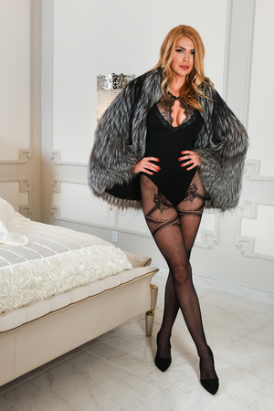 Luxurious blond woman with perfect curvaceous figure and long legs wearing provocative black lingerie bodysuit and fur coat posing in modern bedroom interior. photo