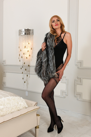 Alluring sexy woman in black lingerie and fur coat in luxury modern bedroom interior. Stylish rich slim girl with hairstyle and bright makeup in apartment. Beautiful fashion blond model. photo
