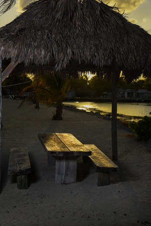 Bungalo with table  and bench at tropical beach location