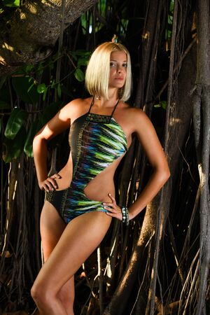 Model posing sexy in front of tropical jungle tree background