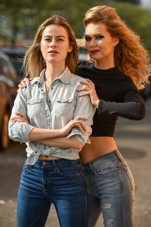 Two young beautiful women in stylish outfits posing on the street. Outdoors, lifestyle.