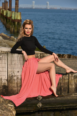maxi: Fashionable young woman wearing cropped top and maxi skirt posing outdoors at boat marina. Stylish fashion portrait. Stock Photo