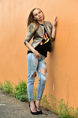 ripped jeans: Beautiful young woman in jacket and ripped jeans posing outdoors, street fashion. Stock Photo