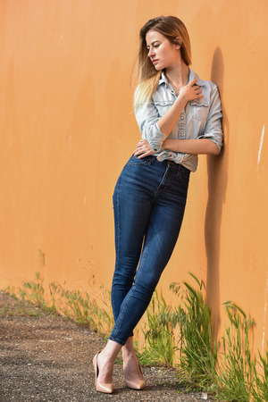 fashion: Attractive fashion woman in denim shirt and jeans posing near orange wall background.