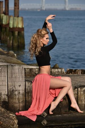maxi: Elegant young woman wearing top and maxi skirt posing pretty at the pier with water on the background.