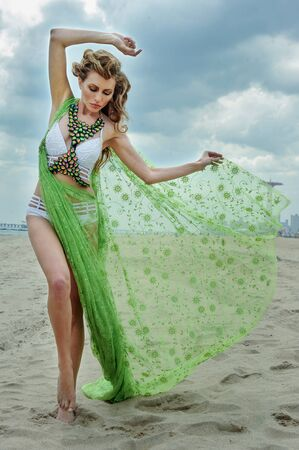 hair cover: Fashion outdoor photo of beautiful sexy woman with blond hair wearing luxury design bikini and holding fluttering cover up on the beach.
