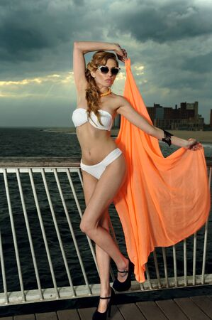with orange and white body: Full body shot of young woman wearing white bikini, orange cover-up and sunglasses, with effective clouds and lighting from coming thunderstorm. Stock Photo