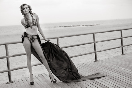 cover up: Young beautiful woman wearing bikini and fluttering cover up posing sexy on the boardwalk at the beach.