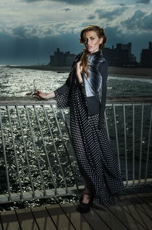 maxi dress: Attractive young woman wearing black and white maxi dress, posing on the pier, with effective clouds and lighting from coming thunderstorm.