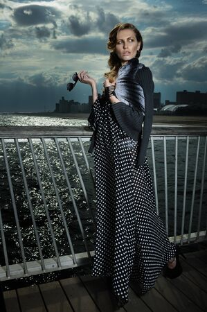 maxi: Attractive young woman wearing black and white maxi dress, posing on the pier, with effective clouds and lighting from coming thunderstorm.
