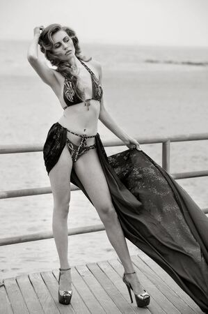 fluttering: Fashion girl with long legs and perfect slim body wearing bikini and fluttering cover up posing sexy on the beach.
