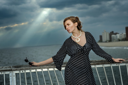 maxi dress: Romantic portrait of young woman wearing black and white dress and sunglasses, with effective clouds and lighting from coming thunderstorm.