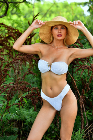 Young blond model posing sexy wearing white swimsuit and straw hat at outside beach location Stock Photo
