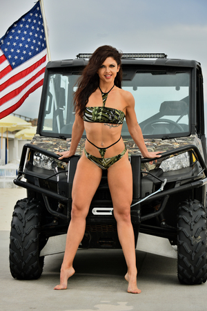Bodybuilder woman in bikini posing sexy on the beach against the jeep.