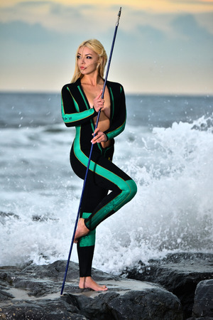 Young woman standing on the rocks wearing neoprene scuba suit and holding fishing spare with waves breaking on background