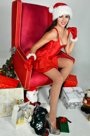 Sexy brunette dressed as Mrs. Santa posing pretty sitting in classical armchair. Christmas decoration. Reklamní fotografie