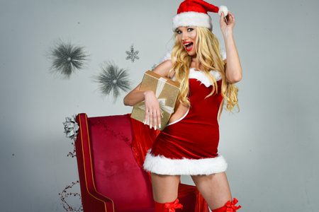 Cheerful pretty young woman in santa claus costume with gift boxes over grey background.