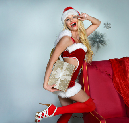 Cheerful Santa Helper girl with gift box posing pretty at Christmas decorated studio background.