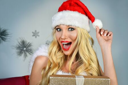 Close-up portrait of excited happy Santas Helper girl with gift.