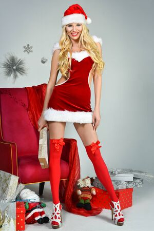 Beautiful sexy girl wearing santa claus clothes. Smiling woman with gifts. Female model in dress and santas hat. Santas helper. Stock Photo