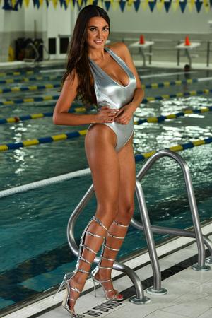 Beautiful sensual woman in sexy  bikini  posing indoor on the edge of swimming pool. Stock Photo