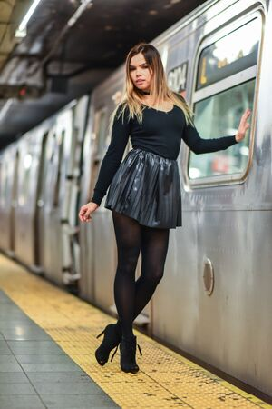 Fashionable young woman in black top and skirt posing on urban city subway metro platform. Stock Photo