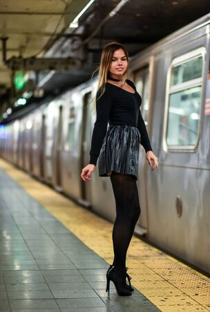 hosiery: Fashionable young woman in black top and skirt posing on urban city subway metro platform. Stock Photo