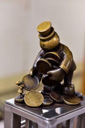 Bronze sculpture of little man collecting pennies