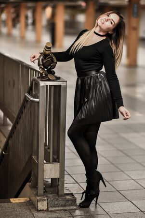 Elegant sensual young woman in black top and skirt posing in NYC Subway. Stock Photo