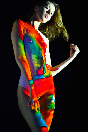 Fashion, creative photo, woman with color image on her face and body. Image projection. Stock Photo