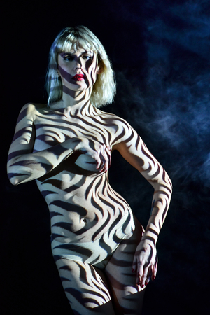 Projection Photography - light patterns projected to nude woman body. Stock Photo