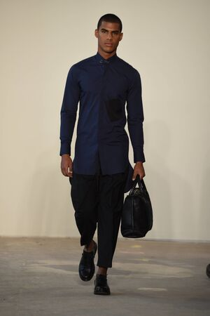 designer bag: NEW YORK, NY - FEBRUARY 02: A model walks the runway at Loris Diran - Runway - NYFW: Mens at Skylight Clarkson North on February 2, 2017 in New York City.