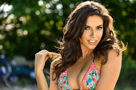 hottie: Gorgeous glamour brunette model posing sexy at nature location wearing bikini
