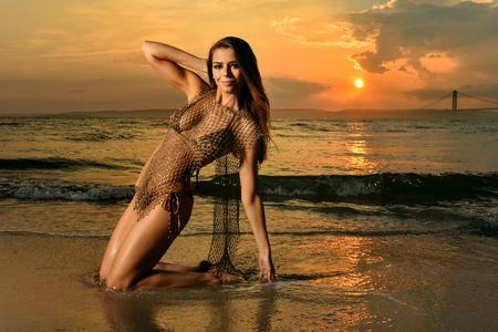 Modelo de roupa de banho posando na localização da praia do oceano usando bikini e rede de pesca Foto de archivo - 83726158