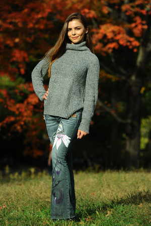 Beautiful young woman in stylish jeans and cozy sweater posing in autumn scenery.