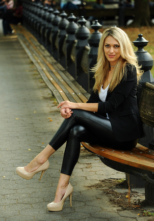 Fashion glamour model posing on the bench at the autumn park.