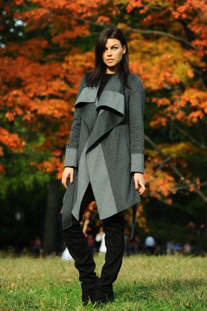 Fashion outdoor photo of gorgeous brunette woman in elegant coat. Autumn background.