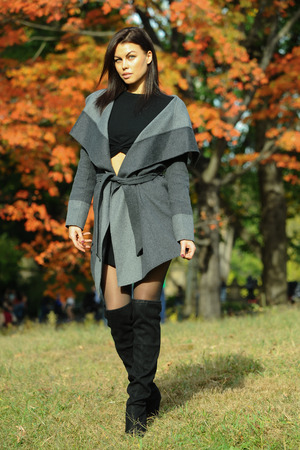 Elegant fashion model posing pretty in the park with colorful autumn trees on the background. Stock Photo
