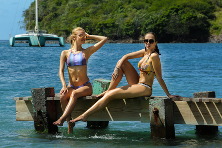 Two pretty young swimsuit models posing on the pier at tropical location.