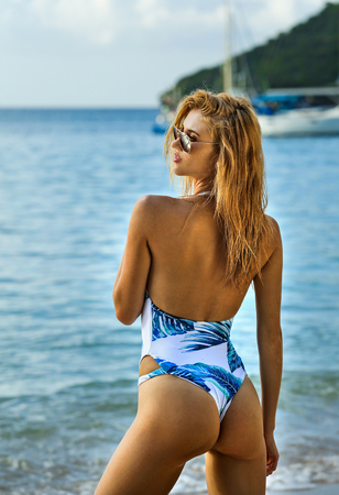 Beautiful young blonde woman in fashionable swimsuit posing on the beach in turning booty shows ass. Sexy model portrait with perfect body. Concept of summer vacation.