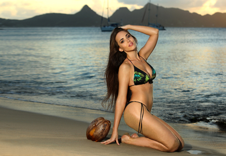 Beautiful sexy young woman posing pretty on the tropical  beach. Fashion glamorous shot at vacation resort.