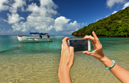 A woman hands holding mobile take photo of paradise beach destination summer wanderlust vacation.